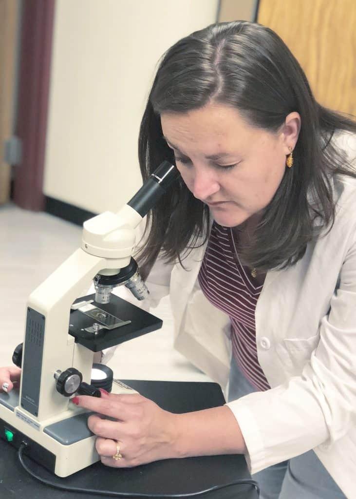 Science teacher with microscope