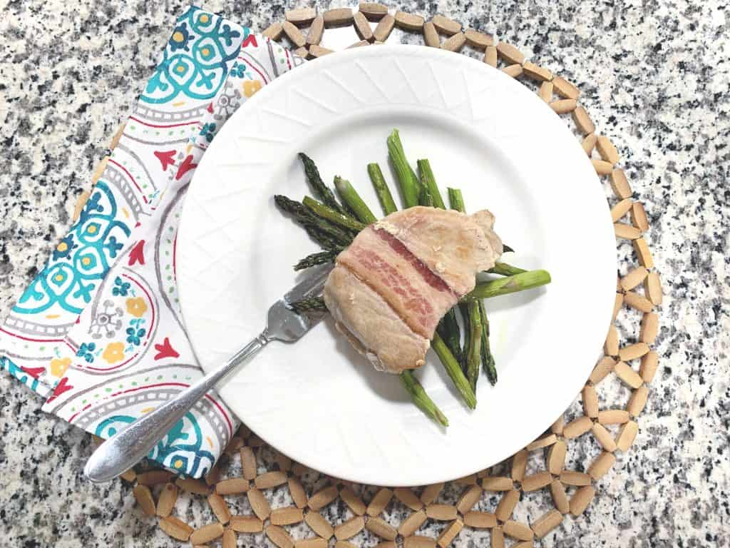 Bacon wrapped pork chops and asparagus