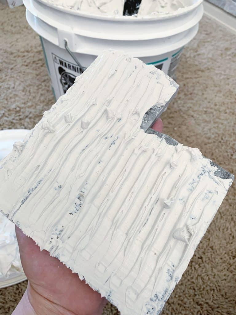 placing adhesive on tile