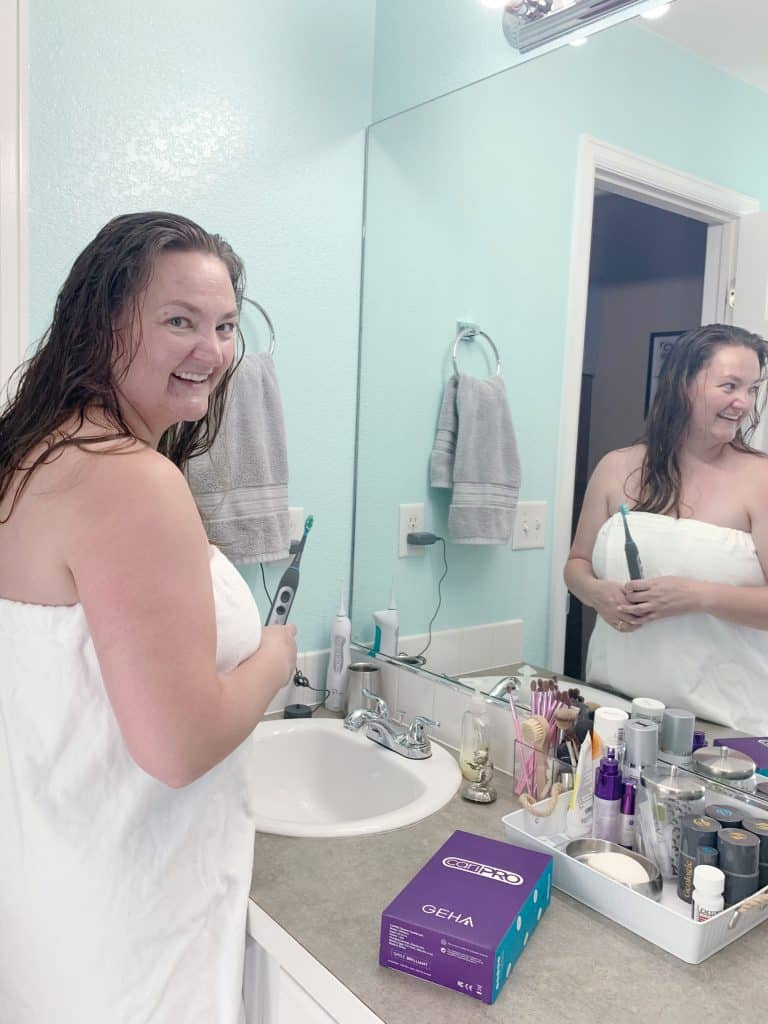 lady in mirror brushing teet